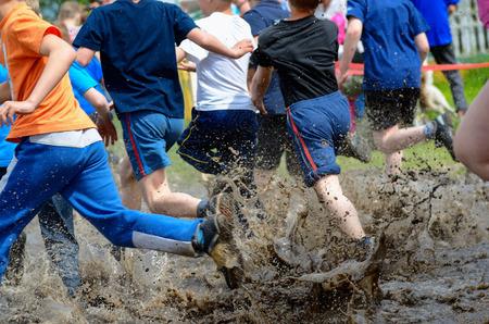 Kids running trail race legs in mud and water Standard-Bild