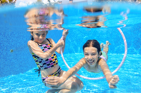 kids playing water: Happy children swim in pool underwater girls swimming playing and having fun kids water sport Stock Photo