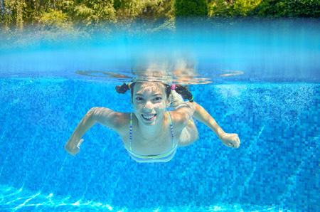 caucasian water drops: Happy girl swims in pool underwater active kid swimming playing and having fun children water sport Stock Photo
