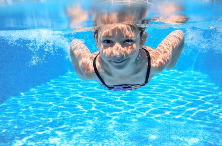 natacion: Feliz niña nada en piscina bajo el agua niño activo jugando la natación y los deportes acuáticos que tienen los niños de la diversión Foto de archivo