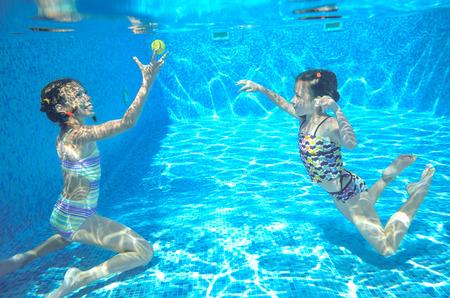 niños felices: Felices los niños nadan en la piscina bajo el agua nadando niñas jugando y tener diversión niños deportes acuáticos Foto de archivo