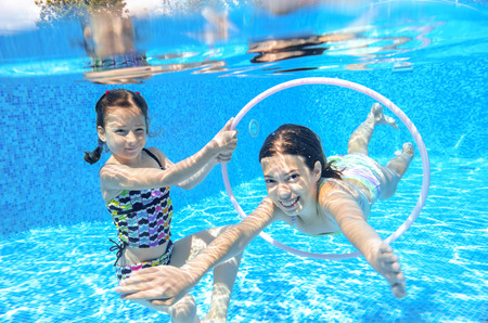 Happy children swim in pool underwater girls swimming playing and having fun kids water sport Standard-Bild