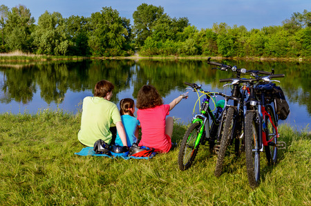 outdoor activities: Family bike ride outdoors, active parents and kid cycling and relaxing near beautiful river
