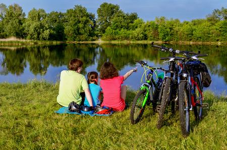 Rodina kole venku, aktivní rodiče a dítě na kole a odpočinek v blízkosti krásné řeky