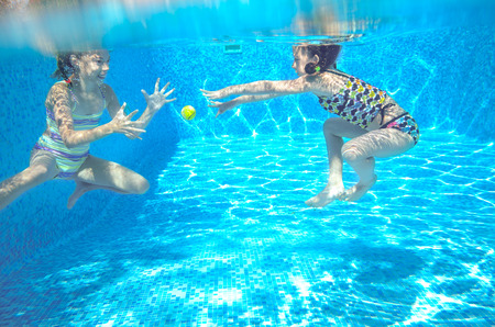 pool diving: Happy active kids swim in pool and play underwater, girls diving and having fun, children on summer  vacation, sport concept Stock Photo