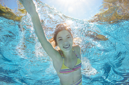 vacation: Child swims in pool underwater, happy active girl has fun in water, kid sport on family vacation