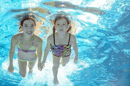 natacion niños: Los niños nadan en la piscina bajo el agua, felices niñas activas se divierten en el agua, los niños el deporte en familia de vacaciones