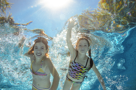 people in action: Children swim in pool underwater, happy active girls have fun in water, kids sport on family vacation Stock Photo
