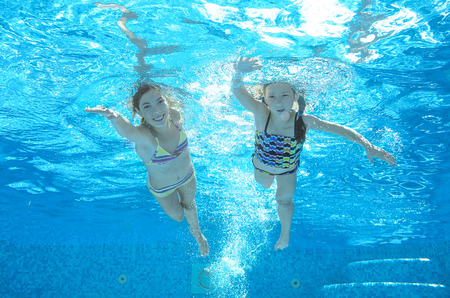 Children swim in pool underwater, happy active girls have fun in water, kids sport on family vacation Stock Photo