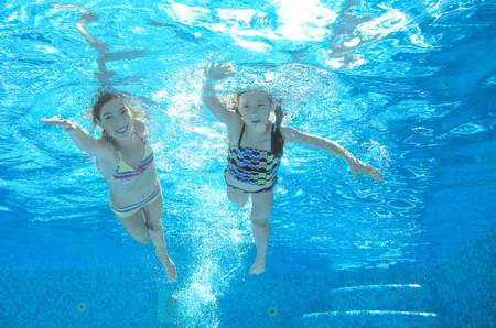 family swimming: Children swim in pool underwater, happy active girls have fun in water, kids sport on family vacation Stock Photo