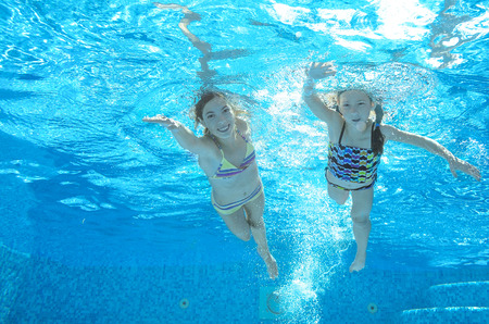 Children swim in pool underwater, happy active girls have fun in water, kids sport on family vacation Archivio Fotografico