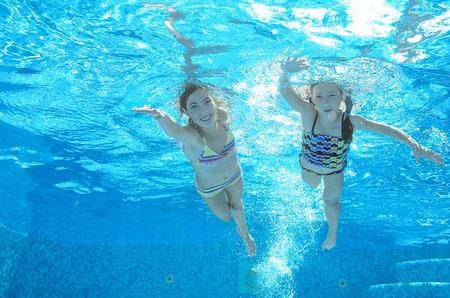 natacion: Los niños nadan en la piscina bajo el agua, felices niñas activas se divierten en el agua, los niños el deporte en familia de vacaciones