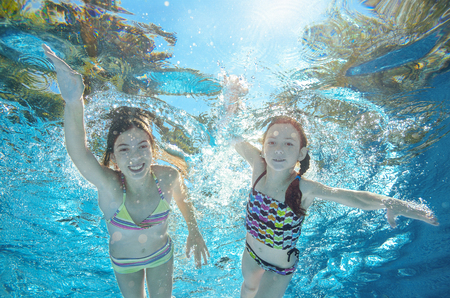 kids activities: Children swim in pool or sea underwater, happy active girls have fun in water, kids sport on family vacation Stock Photo