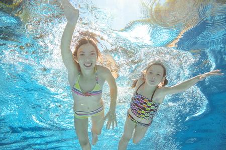 salud y deporte: Los ni�os nadan en la piscina o bajo el agua de mar, felices ni�as activas se divierten en el agua, los ni�os el deporte en familia de vacaciones Foto de archivo