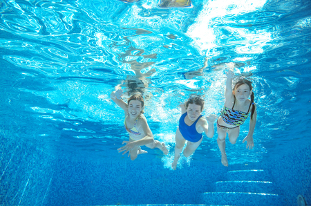 Family swim in pool or sea underwater, happy active mother and children have fun in water, kids sport on family vacation