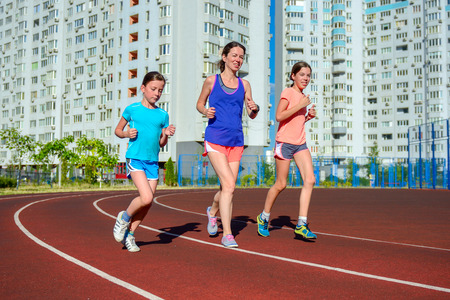 jogging: Family sport, happy active mother and kids jogging on track, running and working out on stadium in modern city Stock Photo