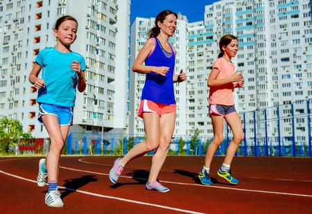 atletismo: Deporte de la familia, la madre feliz activa y niños para correr en pista, funcionamiento y que se resuelve en el estadio en la ciudad moderna