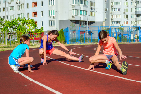 athletics: Family sport, happy active mother and kids jogging and stretching on track, running and working out on stadium in modern city Stock Photo