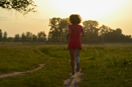 background person: Blurred background: woman runner running on rural road on sunset or sunrise, sport and fitness concept