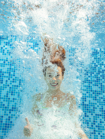 diving pool: Girl jumps and swims in pool underwater, happy active child has fun in water, kid sport on family vacation Stock Photo