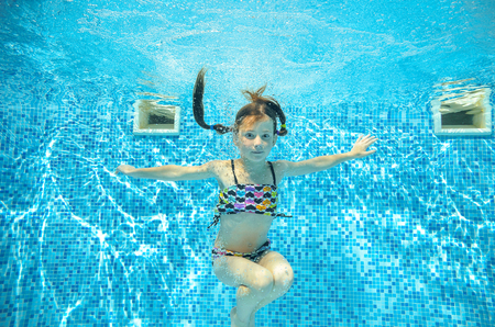 swimming suit: Girl jumps and swims in pool underwater, happy active child has fun in water, kid sport on family vacation Stock Photo