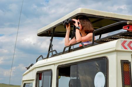 wildlife: Woman tourist on safari in Africa, travel in Kenya, watching wildlife in savanna with binoculars