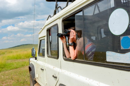 Woman tourist on safari in Africa, travel in Kenya, watching wildlife in savanna with binoculars