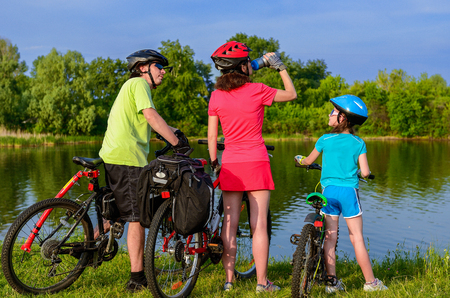 cycling helmet: Family bike ride outdoors, active parents and kid cycling and relaxing near beautiful river