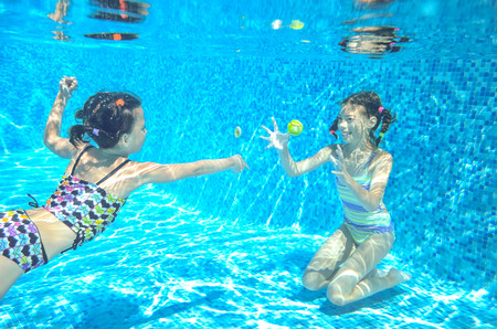 swimming: Children swim in pool underwater, happy active girls have fun in water, kids sport on family vacation Stock Photo