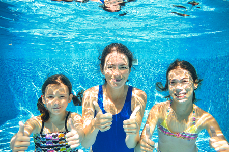 Family swim in pool underwater, happy active mother and children have fun under water, kids sport on family vacation Stock Photo
