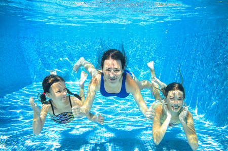 Family swim in pool underwater, happy active mother and children have fun under water, kids sport on family vacation Stockfoto