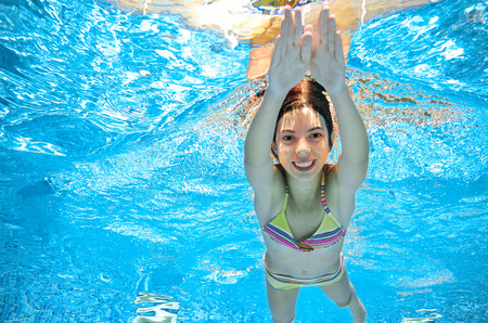 swim: Child swims in pool underwater, happy active girl in goggles has fun in water, kid sport on family vacation