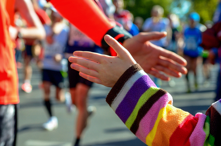 Blurred background: marathon running race, support runners on road, childs hand giving highfive, sport concept Stock Photo