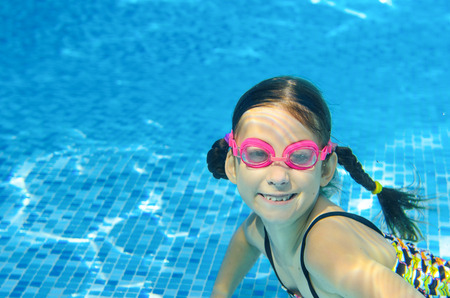 cute kids: Child swims in pool underwater, happy active girl in goggles has fun in water, kid sport on family vacation