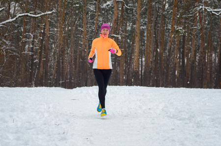 outdoor sport: Winter running in forest: happy woman runner jogging in snow, outdoor sport and fitness concept