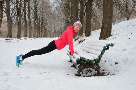 deportistas: Invierno corriendo en el parque: mujer feliz calentamiento finalista y hacer ejercicio antes de correr en la nieve, deporte al aire libre y el concepto de fitness Foto de archivo