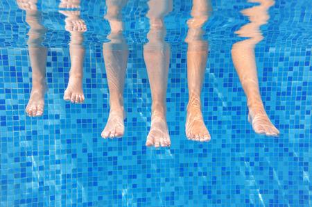 ni�os nadando: piernas de la familia bajo el agua divertidos en la piscina, bajo vista de agua de la madre y los ni�os, las vacaciones y el concepto de deporte Foto de archivo