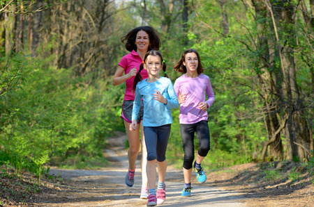 health and fitness: Family sport, happy active mother and kids jogging outdoors, running in forest Stock Photo