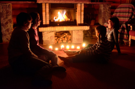 fireplace family: Blurred image of family sitting near fireplace in house, parents and kids relaxing and having fun near fire Stock Photo