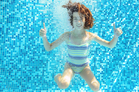 girl sport: Girl jumps, dives and swims in pool underwater, happy active child has fun under water, kid sport on family vacation Stock Photo