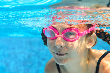 swimming: Child swims in pool underwater, happy active girl in goggles has fun in water, kid sport on family vacation