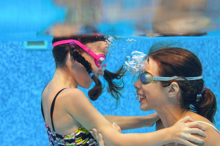 girl underwater: Children swim in pool underwater, happy active girls in goggles have fun under water, kids sport on family vacation Stock Photo