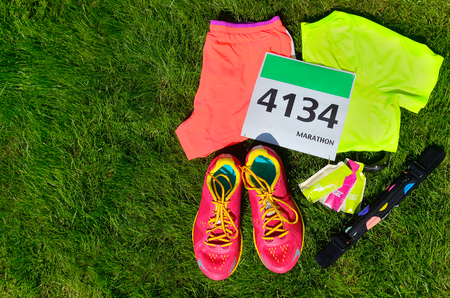 trainers: Running shoes, marathon race bib (number), runners gear and energy gels on grass background, sport, fitness and healthy lifestyle concept Stock Photo