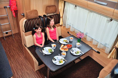 family vacation: Family vacation, RV holiday trip, happy smiling kids travel on camper, children eating in motorhome interior