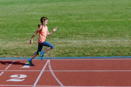 Kids sport, child running on stadium track, training and fitness concept Foto de archivo