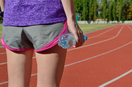 hydration: Fitness and running concept, back view of female runner on stadium track with bottle of water, hydration during workout Stock Photo