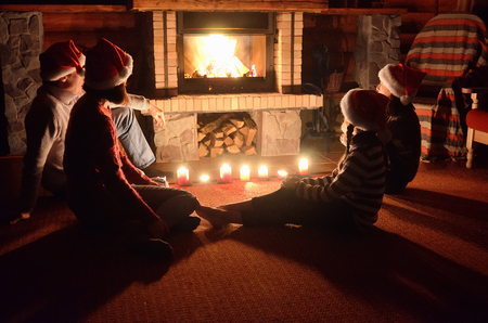 fireplace family: Christmas and New Year holidays, family in santa hats near fireplace in wooden house, parents with kids have fun