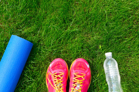 Fitness and healthy lifestyle concept, sport shoes, bottle of water and mat on grass background Stock Photo