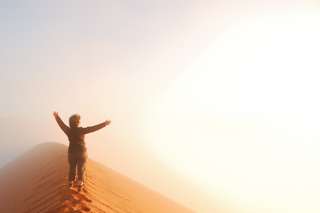 Person standing on top of dune in desert and looking at rising sun in mist with hands up, travel in Africa, Namibia