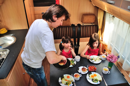 Family eating together in RV interior, travel in motorhome (camper, caravan) on vacation trip with kids Stock Photo